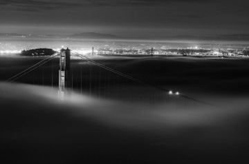 Low fog passes through the Golden Gate Bridge at dawn. In the distance, the Bay Bridge, Yerba Buena Island, and the east bay cities of Oakland and Berkeley can be seen.