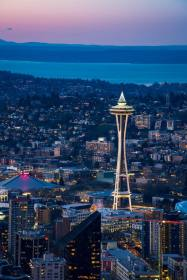 Seattle's Space Needle rises above the surrounding city as the soft glow from twilight is seen over the Puget Sound.