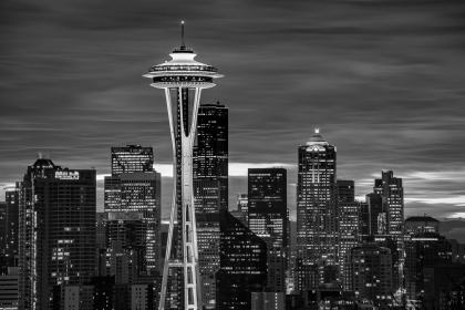 The Space Needle in Seattle sits above the skyline. In black and white, it's unique architecture stands out among the normal city buildings.