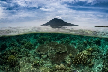 Taken in a single frame, this over under view of tropical Indonesia features the volcanic island of Manado Tua and the coral reefs of Bunaken Marine Park. At the end of a SCUBA dive, I placed my camera half way out and half way in the water.