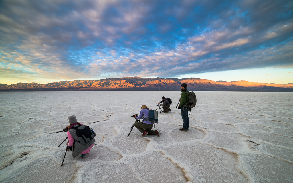photographers on white salt flat with colorful clouds and mountain backdrop