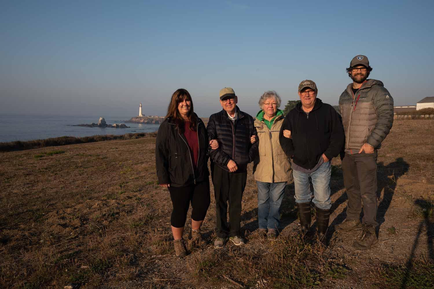 photographers pose for group photo with lighthouse along coast