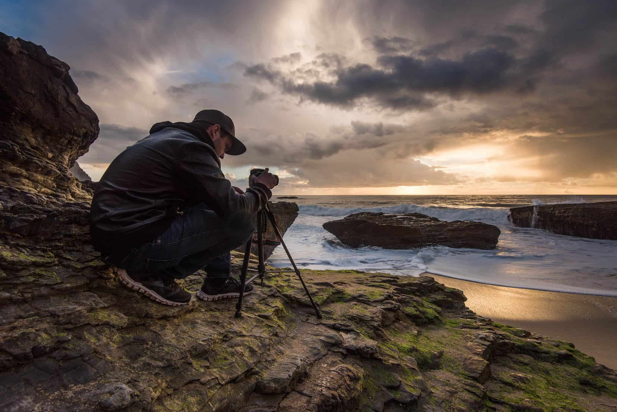 photographer crouched on coastal rocks along California coast