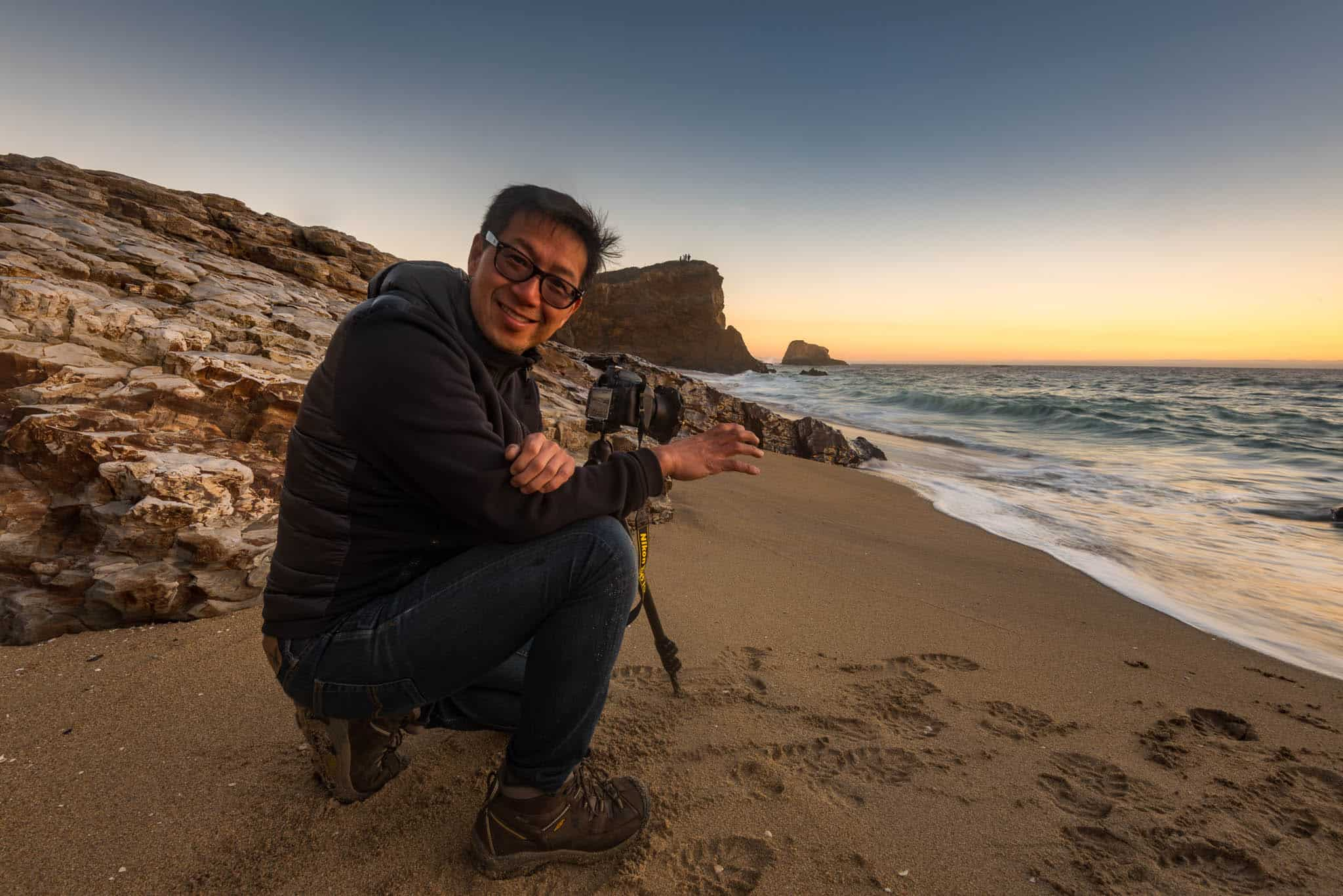 photographer on California coast beach taking photos