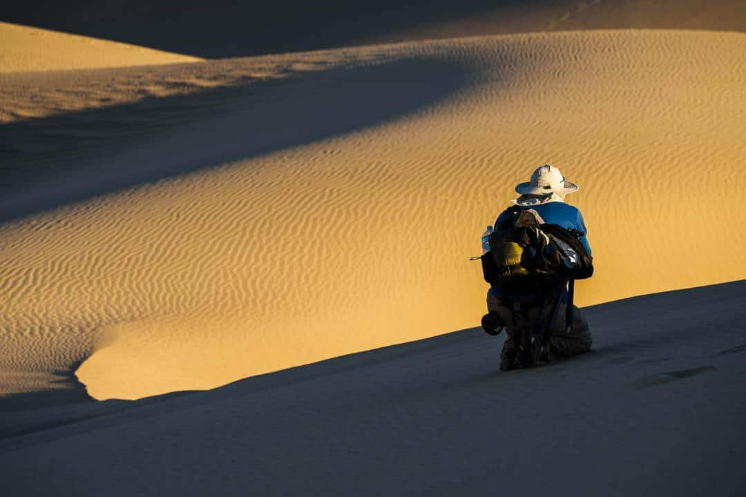 photographer on sand dune with stark light and shadow