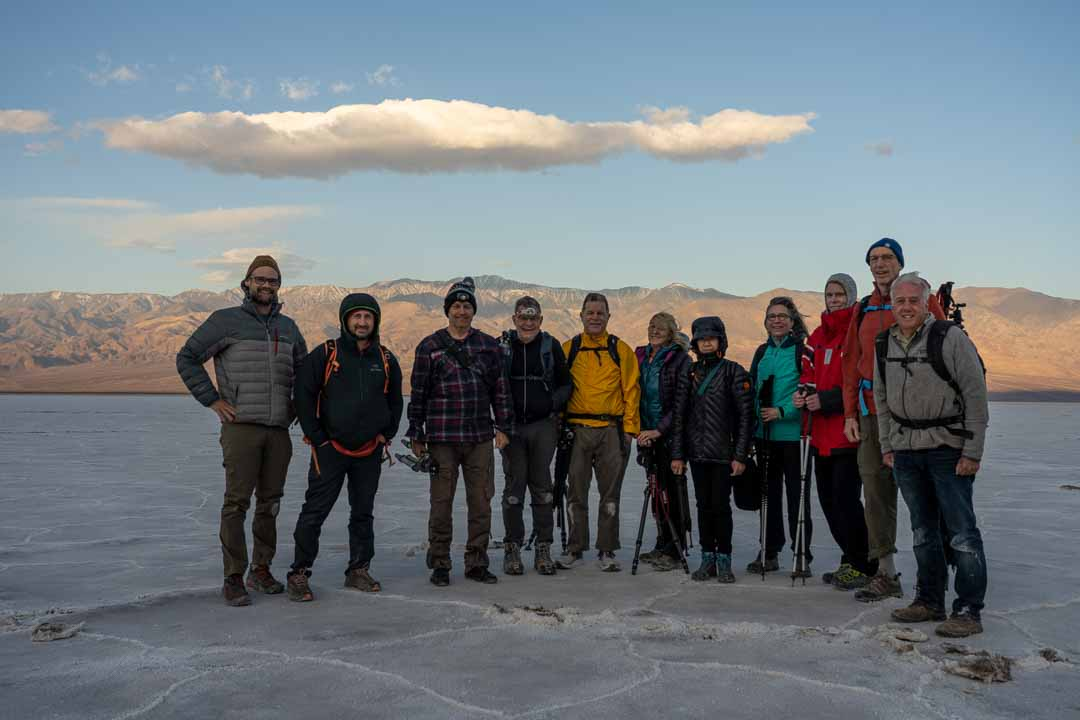 photographers on white salt flat with mountain backdrop