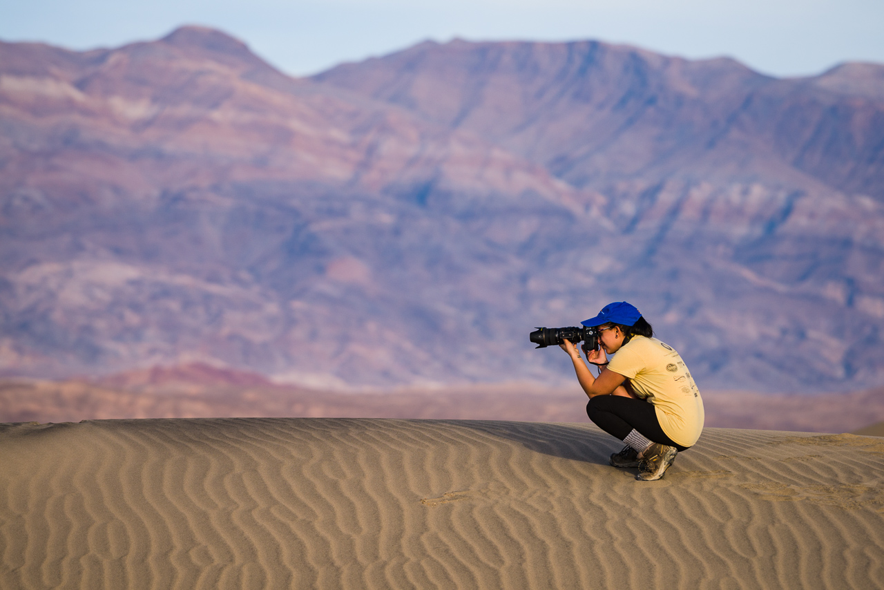 photographer crouching on sand dune with camera