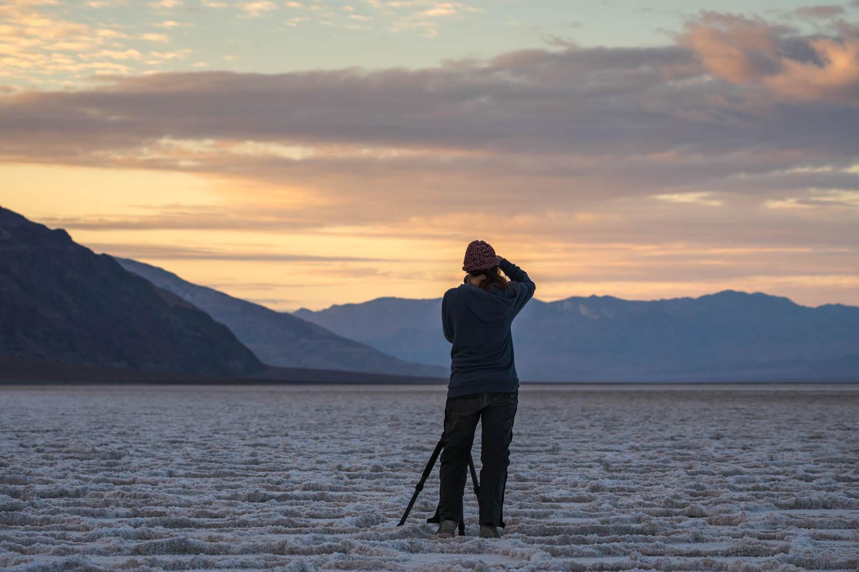photographer on Badwater salt flat during sunrise