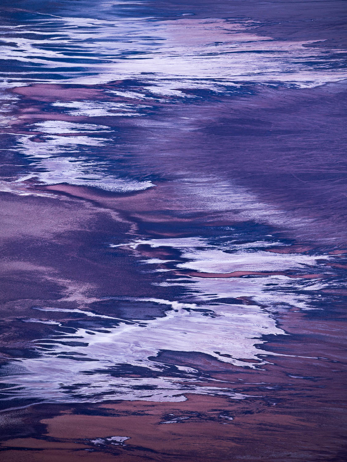 Abstract salt flat patterns stretch upward on purple valley
