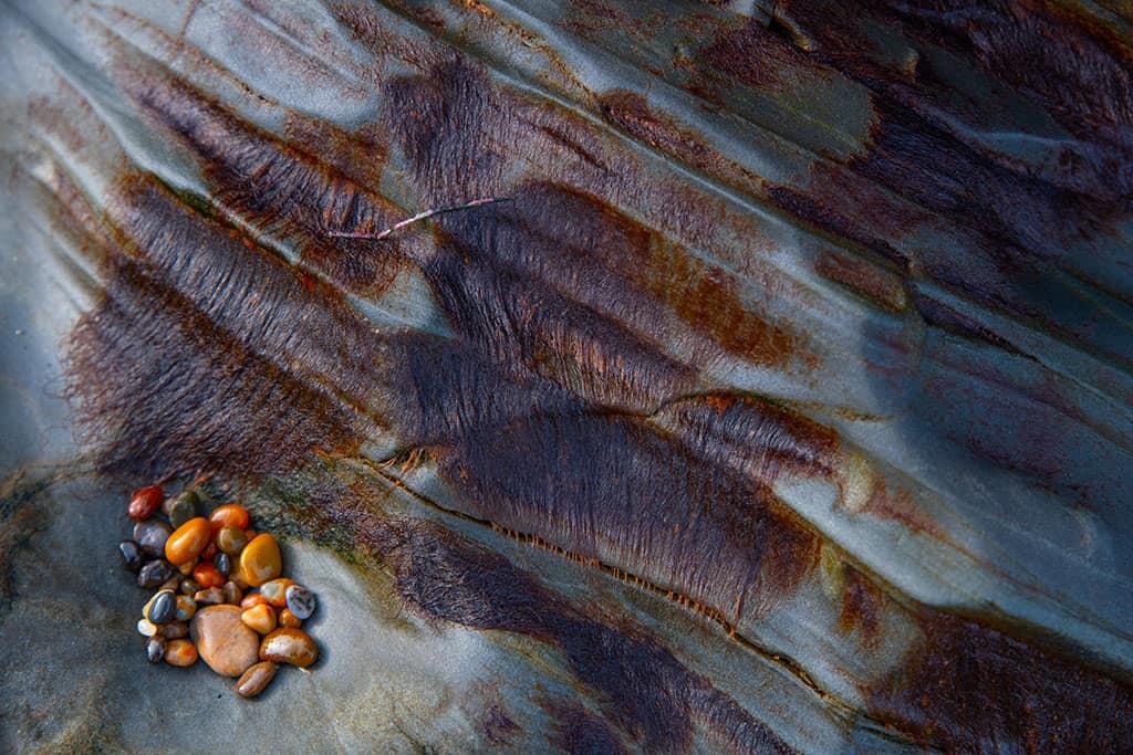 colorful pebbles on rocks along the coast of California