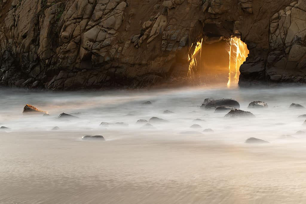 sun shines through archway along the big sur section of the California Coast