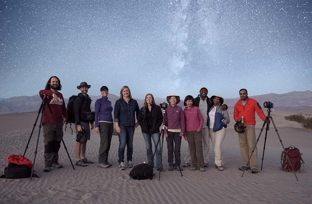 group over photographers on sand dune under milky way