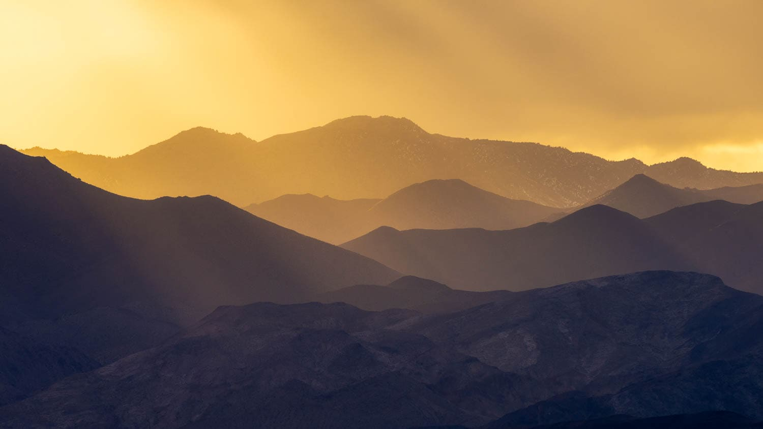 Golden light over layered mountains