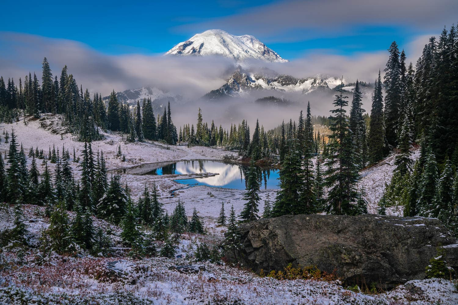 Snow covered hillside with mountain reflected in small lake