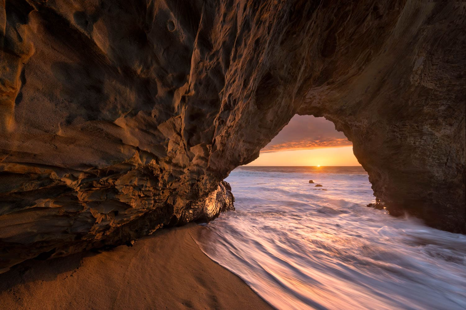 Natural rock arch along central California coast at sunset