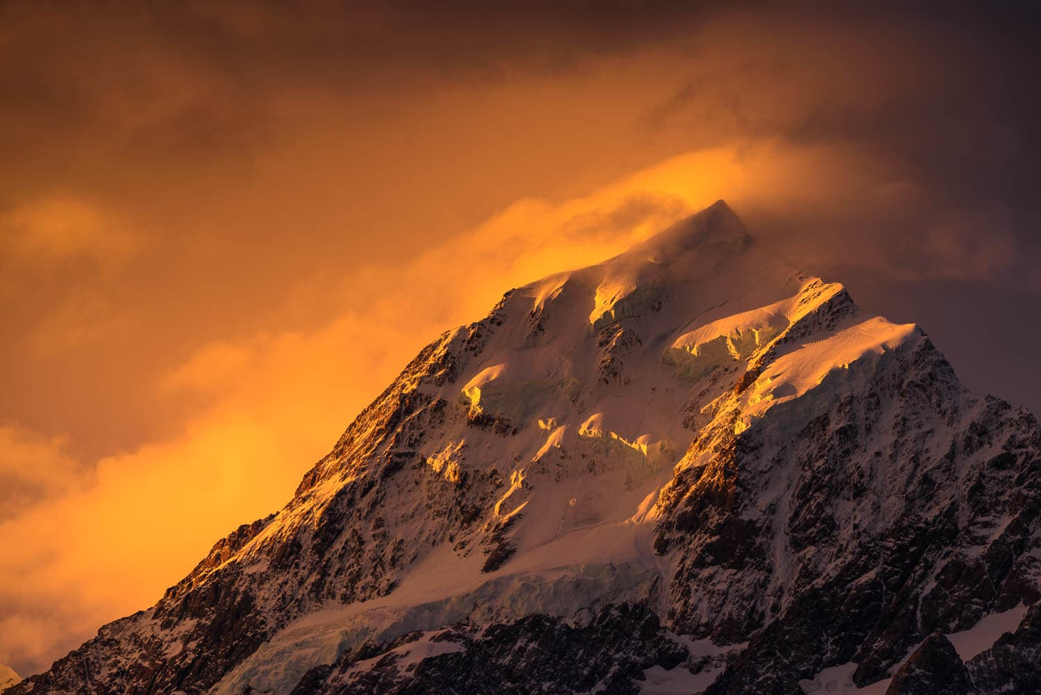 Mount Cook's snowy peak under a fiery sunset sky