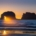 Sunset through offshore rock arch along Oregon coast