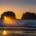 Sunset through offshore rock arch along Oregon coast