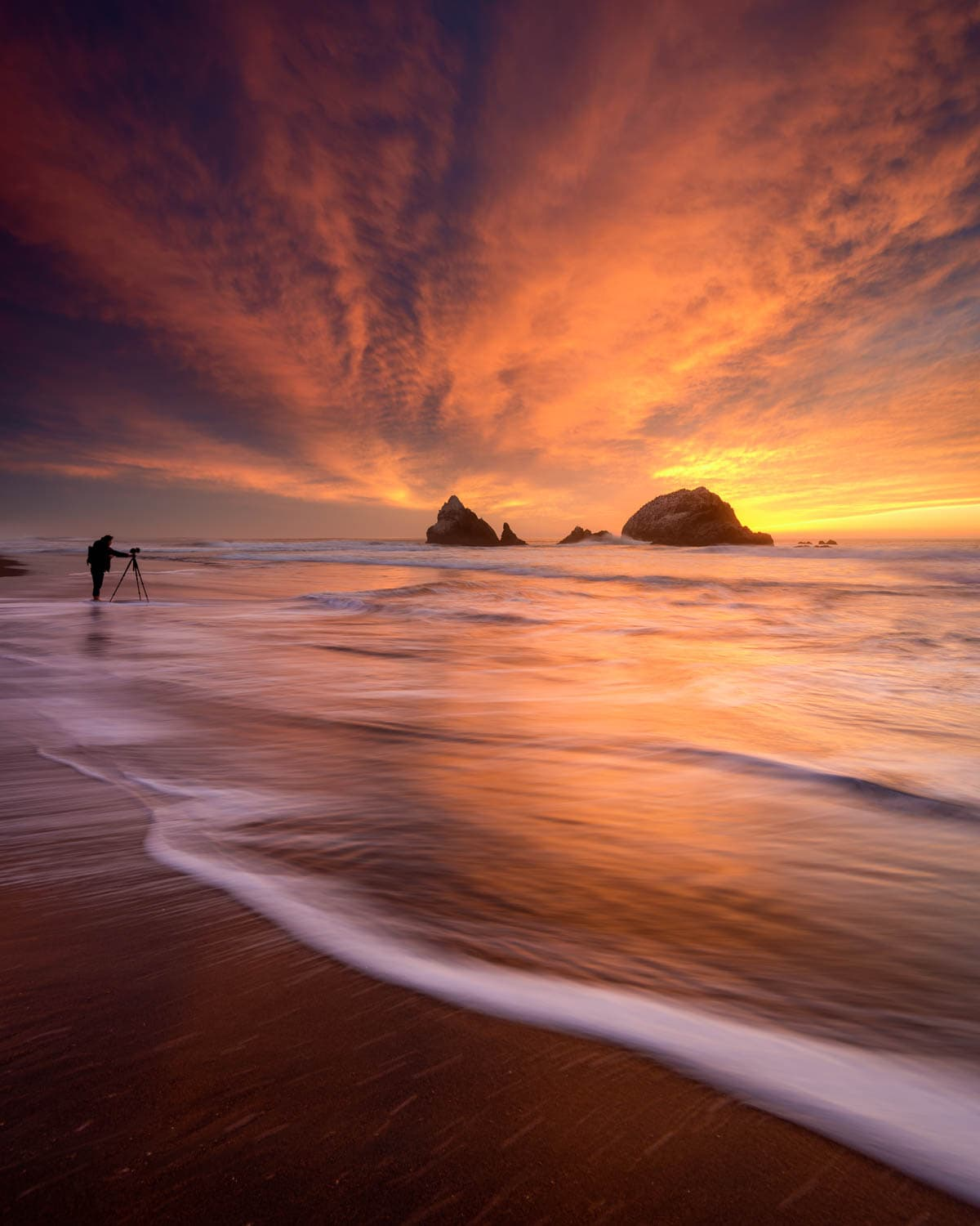 Photographer along the coast with fiery sunset at Seal Rocks