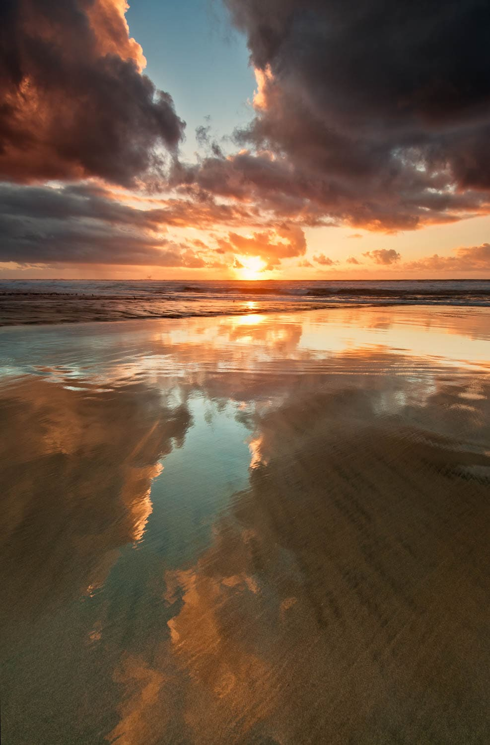 Glassy reflections on sandy beach with sunset sky