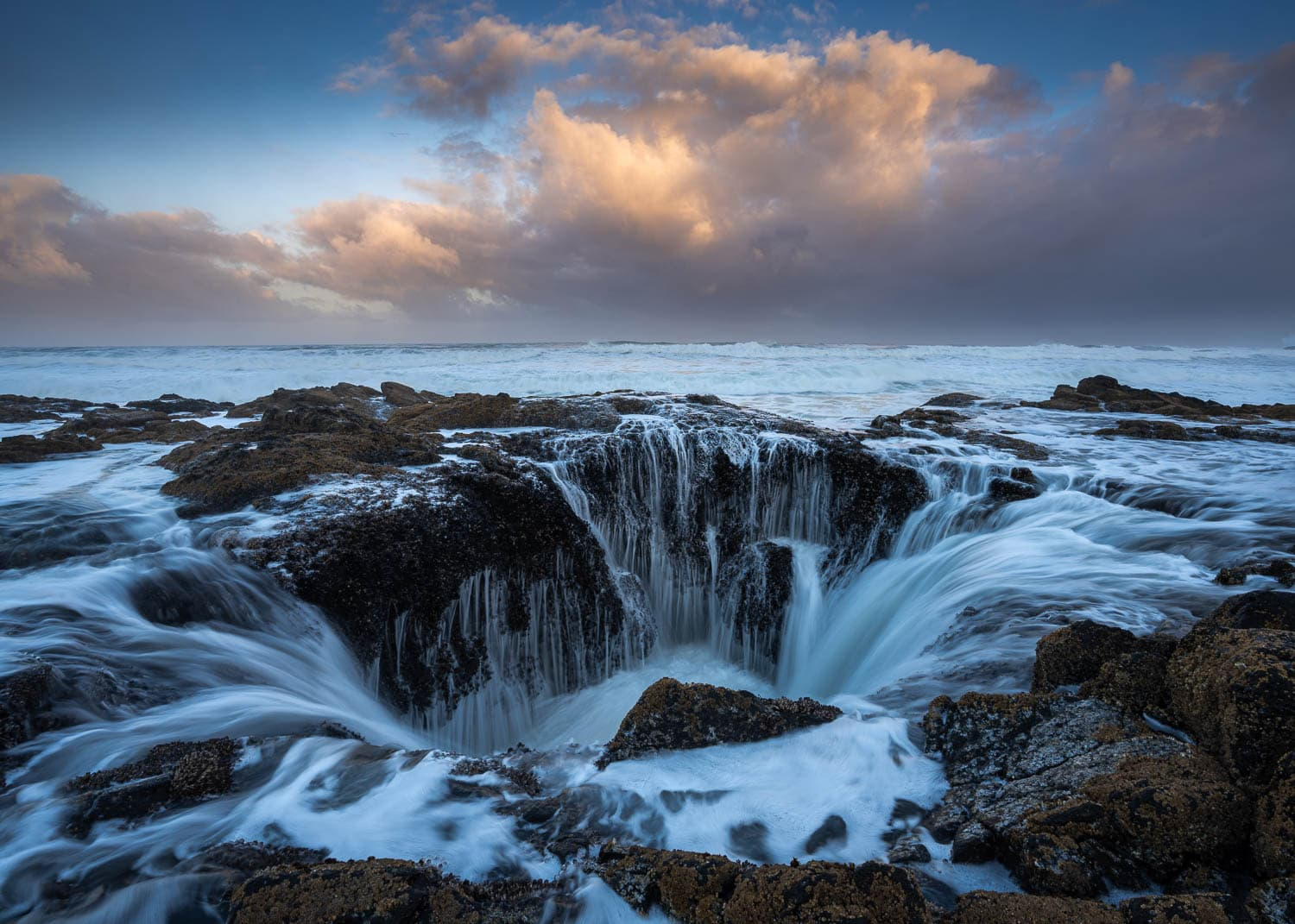 Rocky cauldron with ocean water flowing into it under sunrise skies