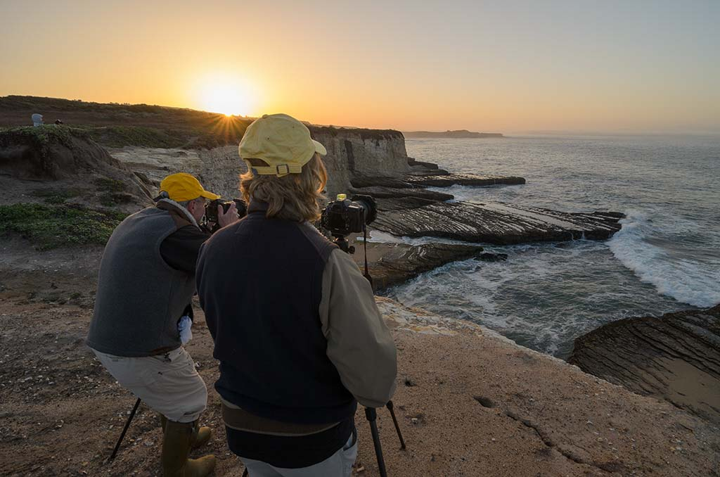 photographers on cliff overlooking ocean with sun rising