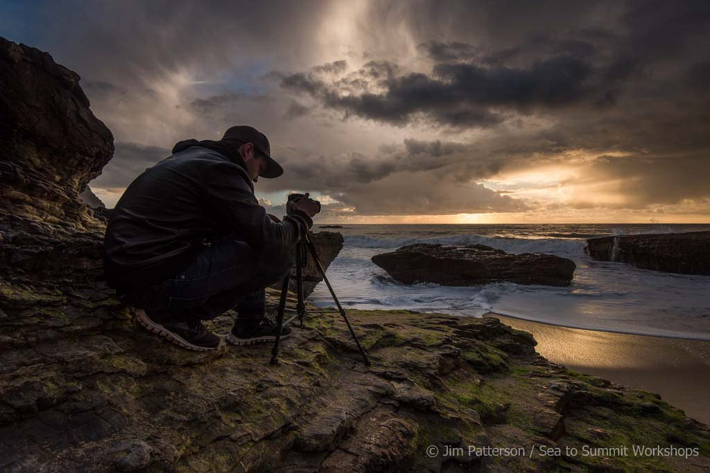 photographer crouching behind tripod under stormy sky along coast